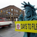 "Max Martinez, dressed as the Statue of Liberty, tries to alert motorists on April 18, 2011, the final day to file taxes. A typical middle-income family could see its taxes go up by $2,000 in 2013 if lawmakers fail to renew a lengthy roster of tax cuts set to expire at the end of 2012. Should that crisis, calld the ""fiscal cliff,"" be resolved, Americans can expect faster economic growth and lower unemployment, experts say."