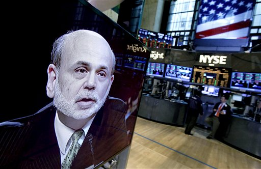 Federal Reserve Chairman Ben Bernanke appears on a television screen on the floor of the New York Stock Exchange in June. On Monday, Bernanke told the Economic Club of Indiana that the Fed needs to drive down borrowing rates because the economy isn't growing fast enough to reduce high unemployment.
