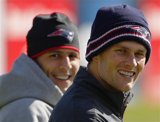 New England Patriots quarterback Tom Brady, right, and tight end Aaron Hernandez walk onto the practice field for a walk-through at the team's NFL football training facility in Foxborough, Mass., on Wednesday.