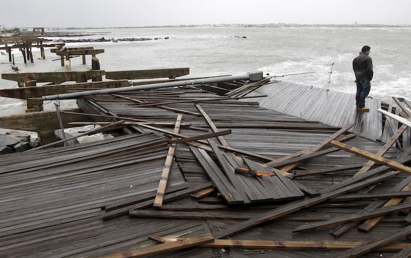 Nicholas Rodriguez looks over a section of the destroyed boardwalk in Atlantic City, N.J., Tuesday, Oct. 30, 2012, not far from where a powerful storm that started out as Hurricane Sandy made landfall the night before. Millions of people from Maine to the Carolinas awoke Tuesday without electricity, but the full extent of the damage in New Jersey, where the storm roared ashore Monday night with hurricane force, was unclear. (AP Photo/Seth Wenig)