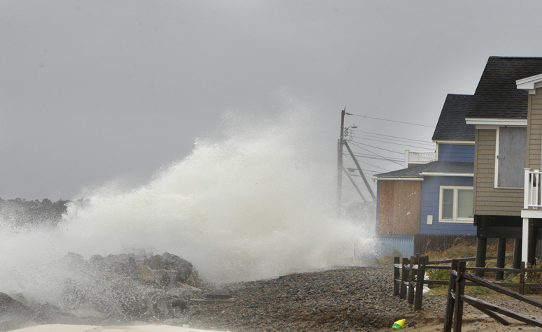 A wave comes over a sea wall in Saco near houses on Eagle Avenue during high tide on Monday. The surge from Hurricane Sandy caused some beach erosion in Saco and there was minor flooding in Camp Ellis.