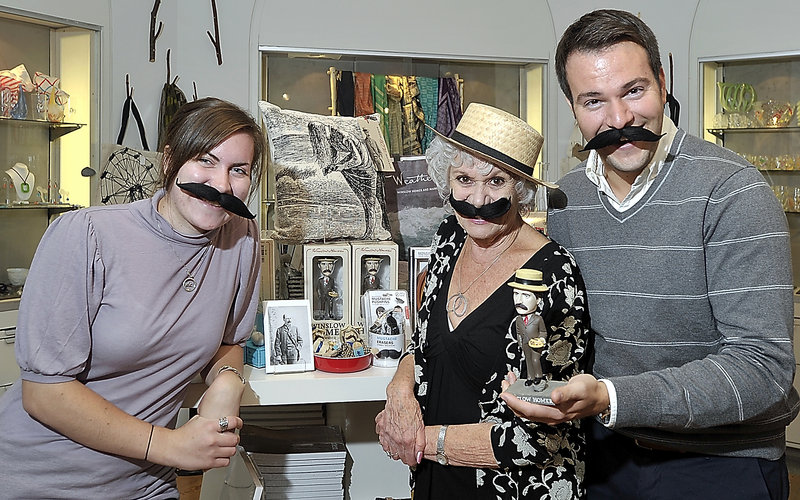 Rachel McDonald, public relations intern at the Portland Museum of Art, left, and Glenda McKertich and Matthew Lorello, both visitor experience associates, ham it up around the Winslow Homer souvenirs display while wearing mustaches similar to those of the Maine artist.