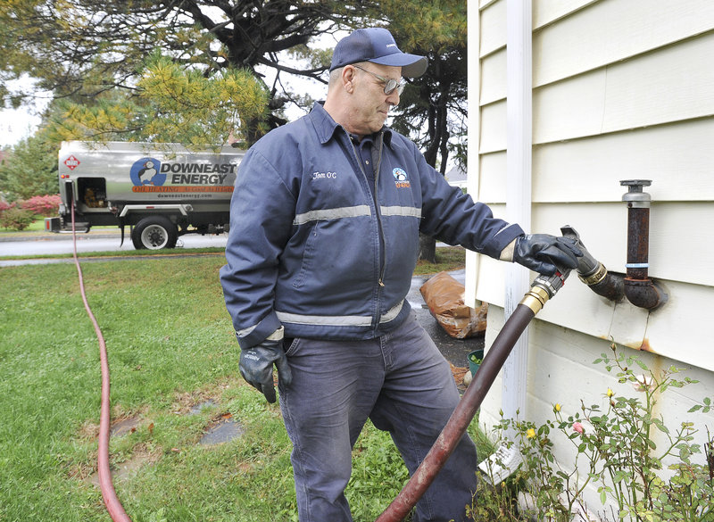 John Patriquin/Staff Photographer Tom O'Connell of Downeast Energy delivers heating oil to a residence on Washington Avenue in Portland on Wednesday. The statewide average price for heating oil is now at $3.68 a gallon, according to the Governor's Energy Office.