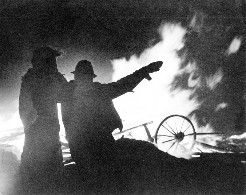 Firefighters are silhouetted against a plume of flames as they plan strategy during one of the 1947 fires.