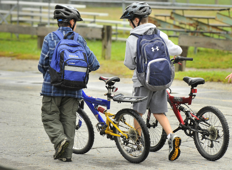 Two students head to the bicycle lock-up area after pedaling to the Portland school.