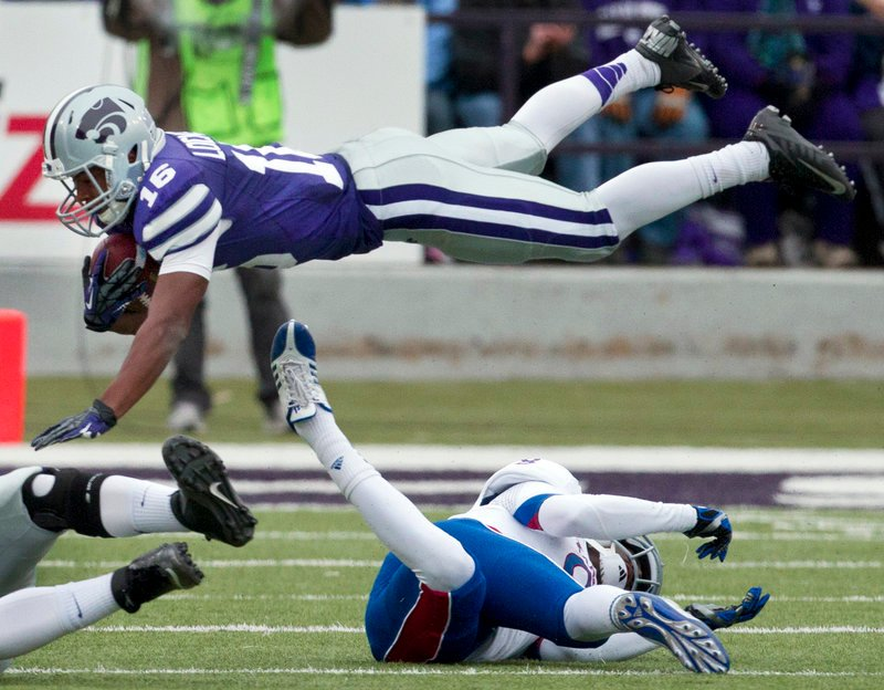 Kansas State's Tyler Lockett goes airborne after being tripped up by Kansas' Josh Ford while returning a first-half kick Saturday. Kansas State won, 56-16.