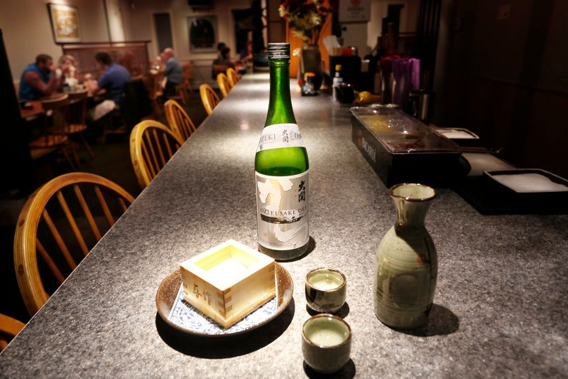 Sake with drinking cups and a cedar box, called a masu, at Yosaku in Portland.