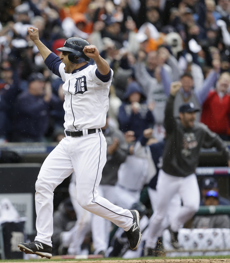 Detroit's Omar Infante crosses the plate with the winning run in the ninth inning against Oakland, scoring on a sacrifice fly by Don Kelly in a 5-4 win Sunday that gave the Tigers a 2-0 series lead.