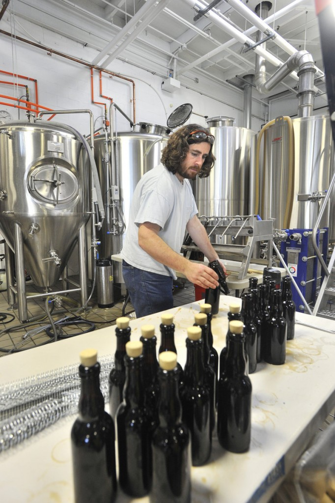 Nathan Sanborn, owner of Rising Tide Brewing Co. in Portland, bottles a special brew of bourbon barrel-aged stout. The company recently moved into a new and larger space and expects to increase production from 149 barrels last year to around 800 this year.