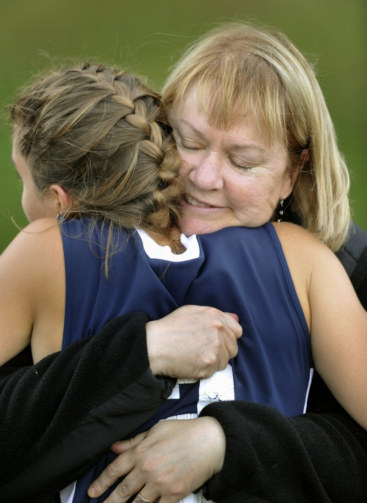 """Christina DiPietro gets a hug from her mom, Ann DiPietro, after Fryeburg's game against Yarmouth late last month. Her daughter's vision disorder was evident early in life, said Ann DiPietro, who said retinitis pigmentosa has already robbed Christina of her night vision. """"That degeneration has been completed."""""""