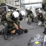 A demonstrator is arrested Tuesday in Athens, one of 200 detained in protests during Angela Merkel's visit.