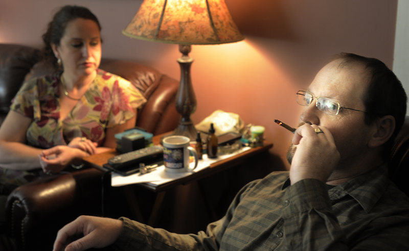Glenn Lewis smokes medical marijuana in his Manchester home Oct. 9, while recovering from surgery. Both he and his wife, Catherine, sustained what have become recurring injuries after a car crash many years ago, and they treat the injuries with medical marijuana.