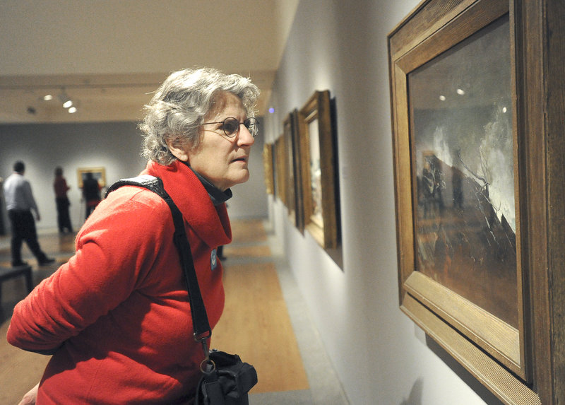 """Jane Rosser of Brattleboro, Vt., on Friday takes a close look at Winslow Homer's 1893 oil painting """"Coast of Maine,"""" which is included in the Portland Museum of Art's exhibit titled """"Weatherbeaten: Winslow Homer and Maine."""" The museum estimates that 75,000 people will view the show before it closes at the end of the year. Because of its popularity, the exhibition requires advance tickets, and visitation is limited to 60 people each half-hour."""