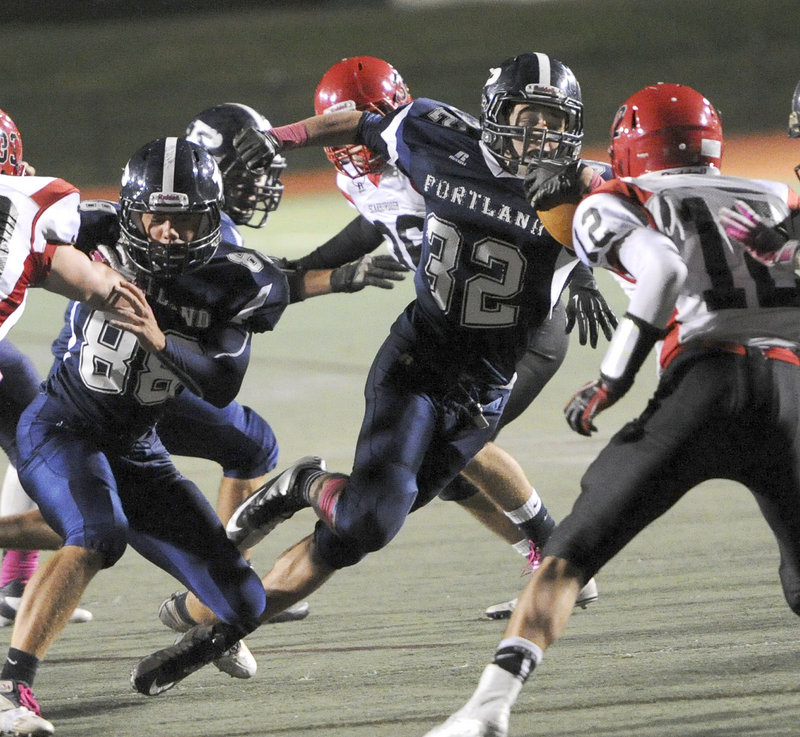 Justin Zukowski, who gained 157 yards and scored a touchdown Friday night for Portland, receives a block from Anthony Green to gain ground during the 25-20 victory against Scarborough at Fitzpatrick Stadium. The Bulldogs are hoping for a home playoff game.