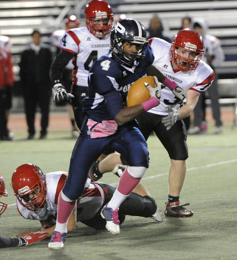 Jayvon Pitts-Young of Portland bursts through a hole in the line and gains extra yardage against Scarborough.