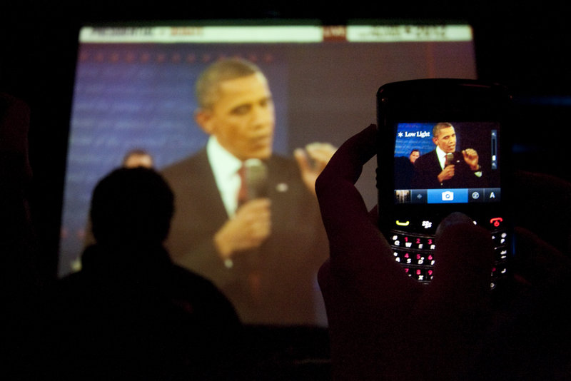 A spectator uses a phone to shoot a photo of a big-screen image of President Obama shown at Empire Dine and Dance in Portland.