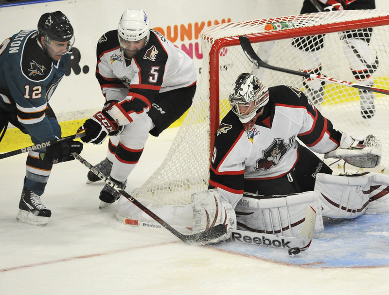 Pirates goalie Mark Visentin makes a stick save on a wraparound attempt by Worcester's Freddy Hamilton as Chris Summers defends.