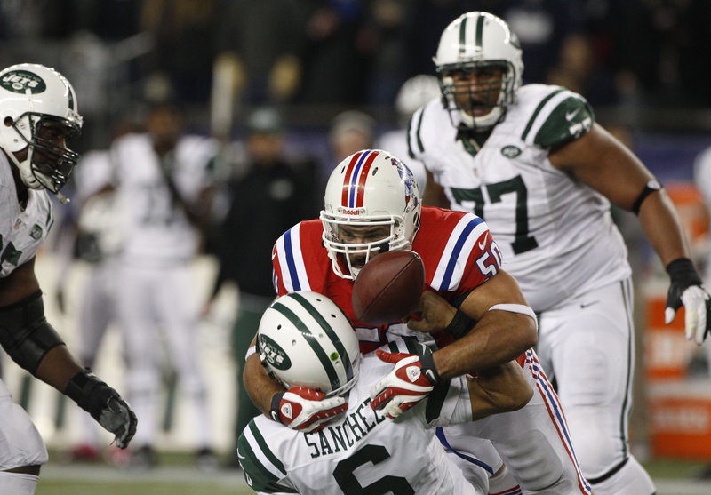 Rob Ninkovich separates Jets quarterback Mark Sanchez from the ball to preserve the Patriots' 29-26 overtime victory over New York Sunday at Gillette Stadium in Foxborough, Mass.