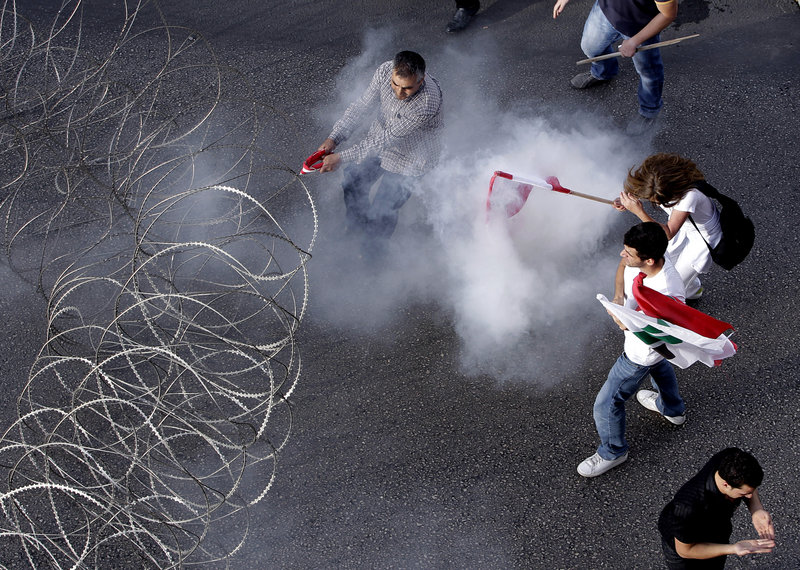Protesters are enveloped in tear gas as they pull a barbed-wire barrier during clashes after the funeral of Brig. Gen. Wissam al-Hassan in Beirut on Sunday.
