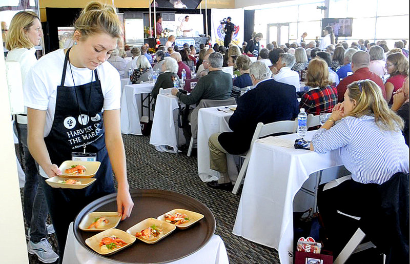Servers at Thursday's Maine Lobster Chef of the Year competition deliver samples of the dishes being made by the contestants to the audience for judging at the annual Harvest on the Harbor event.