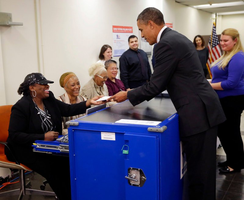 President Obama turns in his ballot receipt to election official Marie Holmes, left, as he prepares to cast his vote at the Martin Luther King Community Center in Chicago.