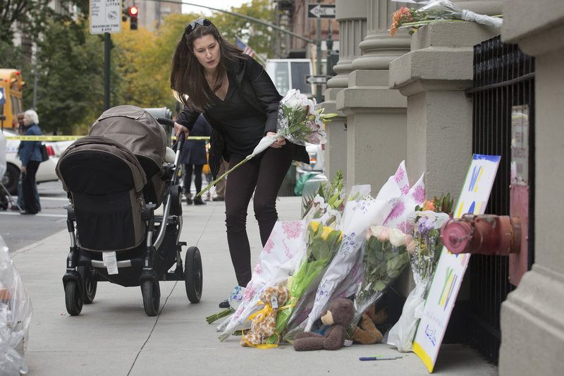 A mourner places flowers at a memorial outside the apartment building of the two children allegedly stabbed by their nanny, who then slit her own throat, police said.