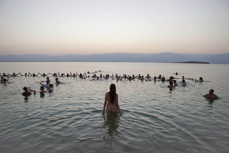 Environmental and social activists from Israel and around the world gather at the Dead Sea for a protest float led by photographer Spencer Tunick against the deterioration of the sea's condition last month.