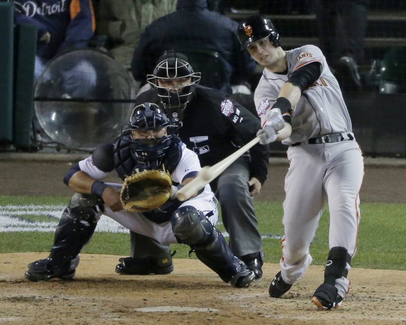 San Francisco's Marco Scutaro punches a single to center field in the top of the 10th inning, driving home Ryan Theriot with the go-ahead run as the Giants completed a sweep of the World Series with a 4-3 win Sunday night against the Tigers.
