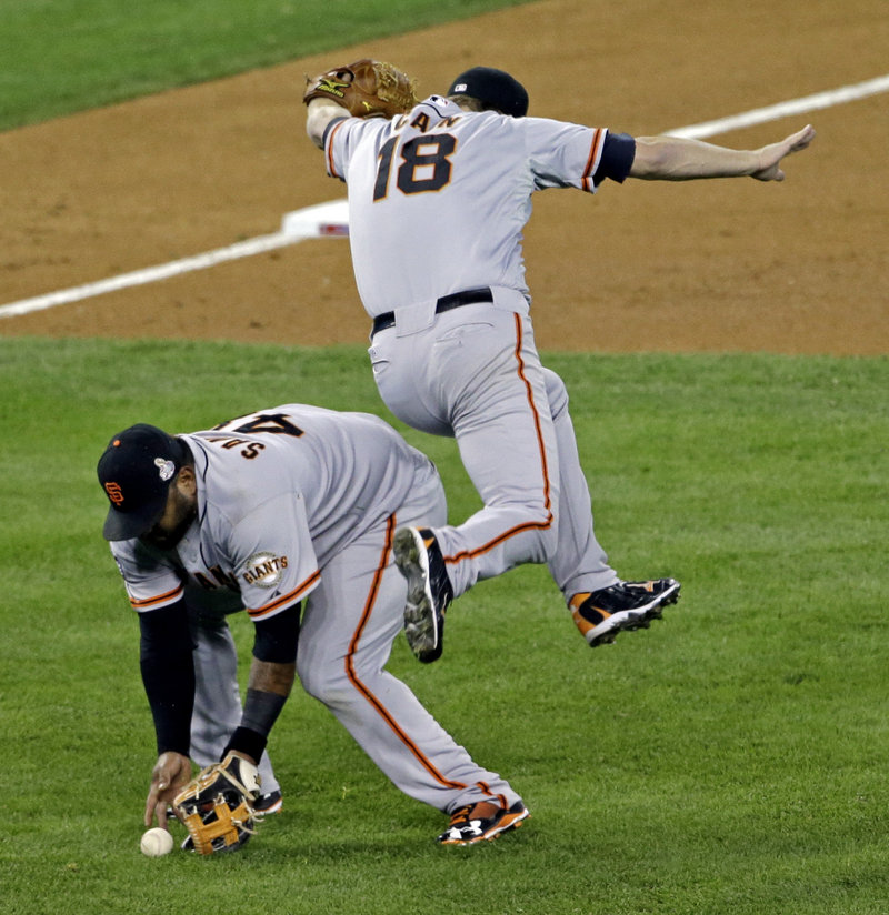 San Francisco pitcher Matt Cain gets out of the way as Pablo Sandoval fields a bunt by Detroit's' Quintin Berry during the third inning. Sandoval, who was 8 for 16 with three home runs in the series, was chosen as MVP.