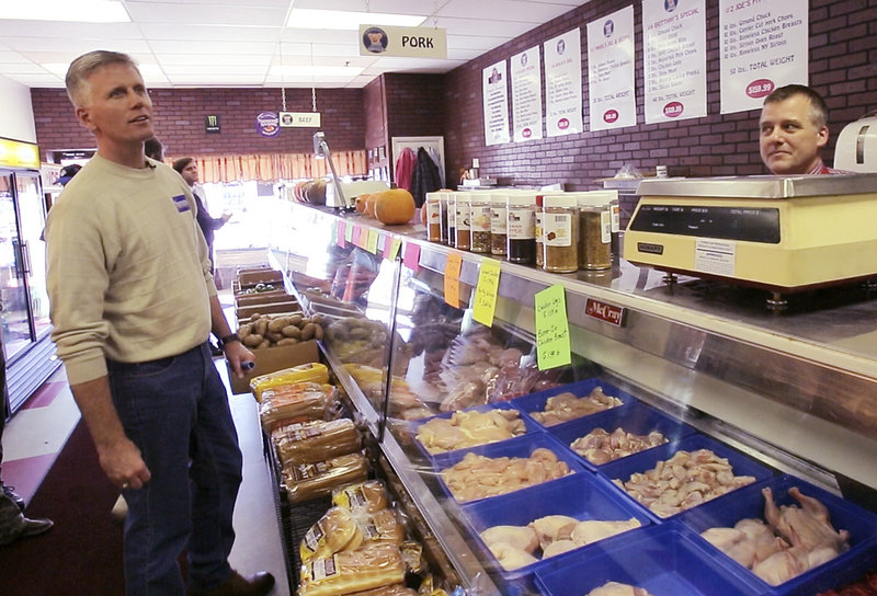 Charlie Summers checks the menu at Hoggy's after Mark Hoglund, owner of the deli/sandwich shop, told him about one of the deli's specialty sandwiches on Saturday. Summers was campaigning in Windham and had stopped in at a few businesses along Route 302.