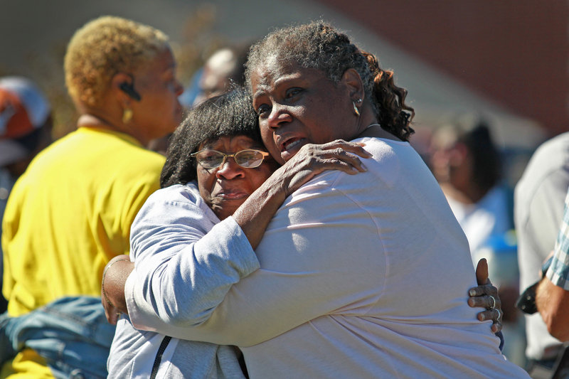 Flora Ford, left, is comforted by a friend outside the Greater Sweethome Missionary Baptist Church in Forest Hill, Texas, on Monday, after the church's founding pastor was killed by an attacker.