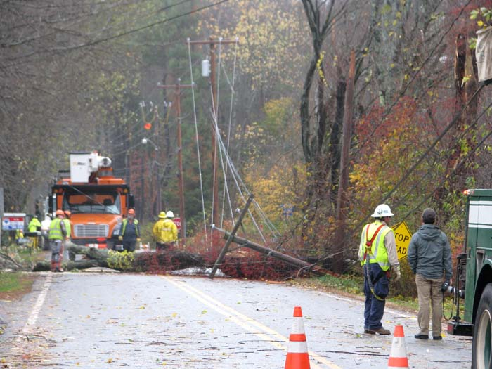Crews from McDonough Electric Construction of Bedford, Mass., on Tuesday morning remove a cherry tree that had fallen over Princes Point Road near Gilman Road in Yarmouth. The tree was tangled in electrical lines.