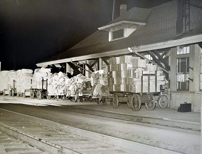 The Freeport train station in 1950, with trucks filled with L.L. Bean packages ready to be loaded onto freight cars.