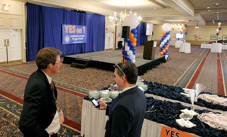 David Farmer and Miguel Rodriguez of Mainers United for Marriage talk in front of an empty stage on Tuesday at Holiday Inn by the Bay, where an estimated 1,000 supporters were expected to gather for an election night celebration.
