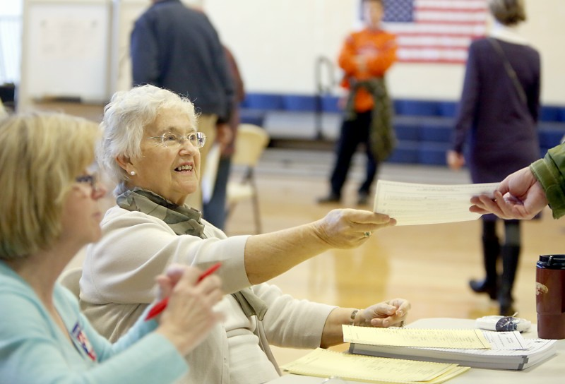 Volunteer Joan Macisso hands a ballot to a voter during voting at the East End Elementary School Tuesday morning in Portland on November 6, 2012. Tim Greenway/Staff Photographer
