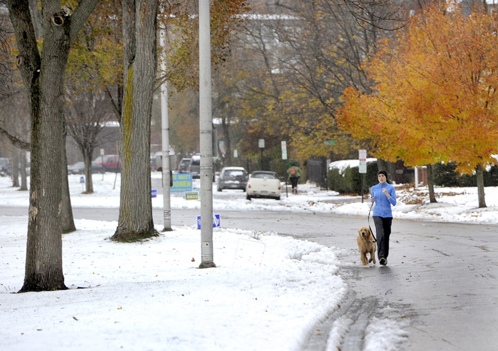 Anya Wilhelmi and her dog Grover avoid the wet snow as they jog along the Western Prom on Thursday morning.