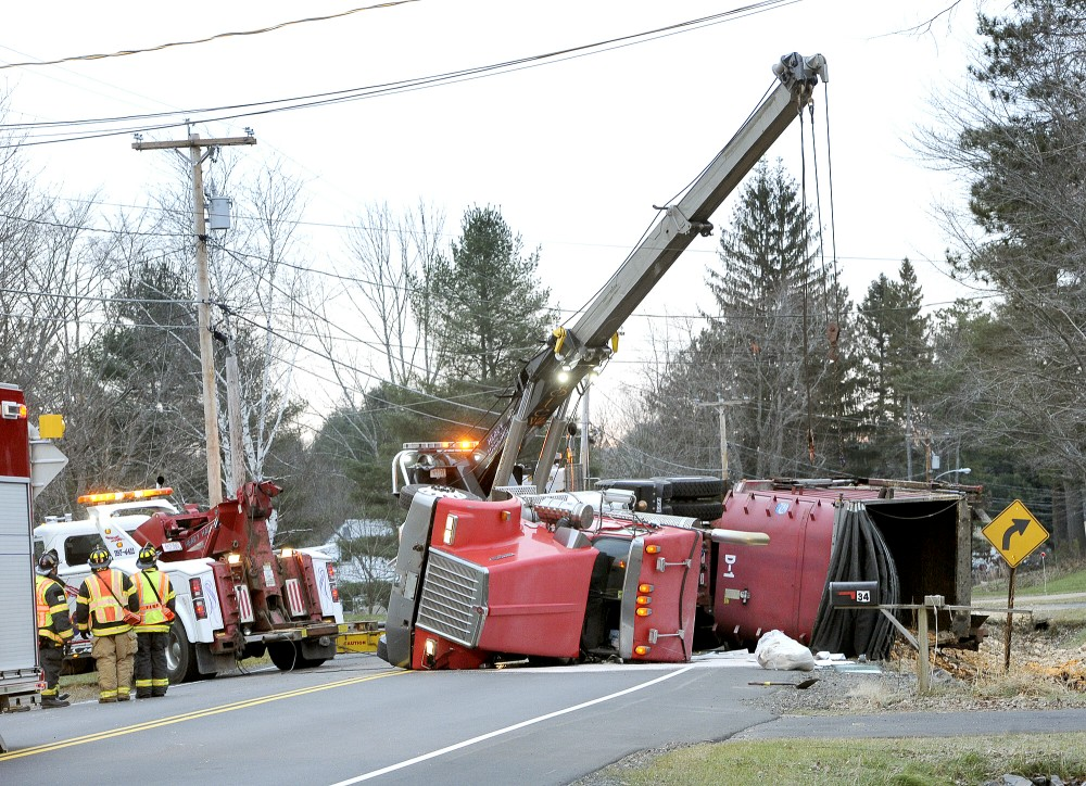 Workers try to upright a trash truck that overturned on Rt. 237 in Gorham early this morning, Tuesday, Nov. 27, 2012 causing traffic to be re-routed around the scene.