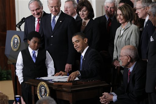 President Obama reaches for a pen to sign the health care bill into law at White House on March 23, 2010.