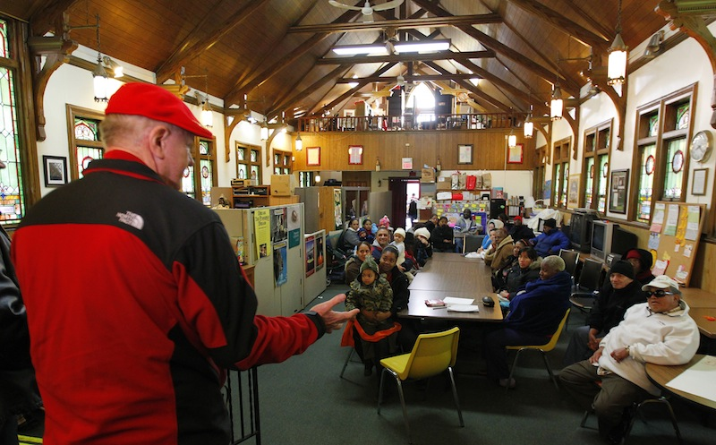 A wealthy philanthropist from Kansas City, Mo., known as Secret Santa, distributes $100 dollar bills to needy people at St. Joseph's Social Service Center in Elizabeth, N.J., Thursday, Nov. 29, 2012.