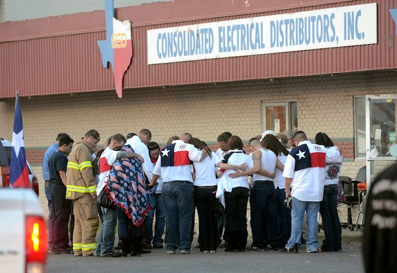 Parade participants and pubic safety officials huddle after a trailer carrying wounded veterans in a parade was struck by a train in Midland, Texas, Thursday, Nov. 15, 2012.