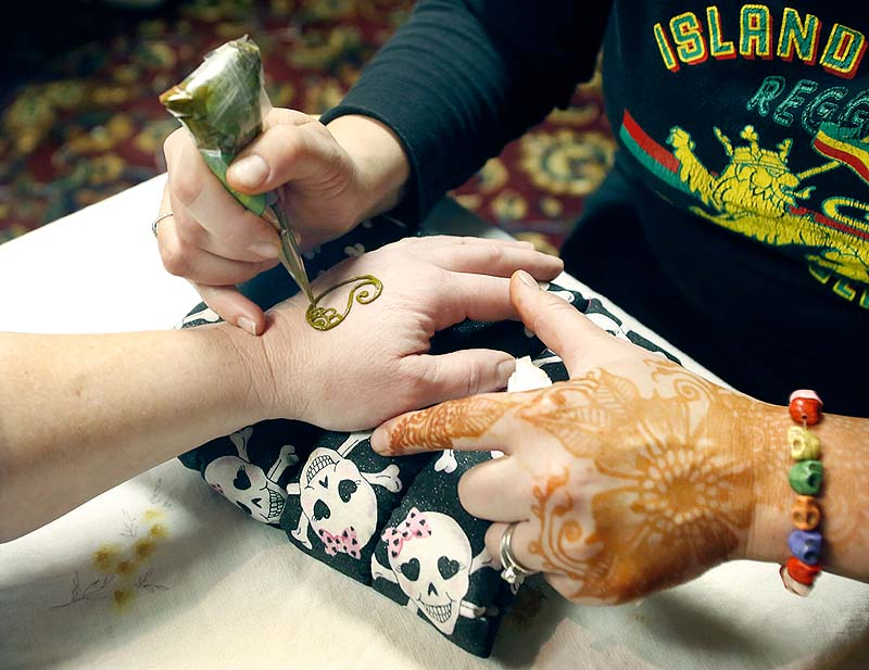 Artist Amy Walker creates henna art on a client's hand during Psychic Sunday at the Fireside Inn and Suites in Portland.