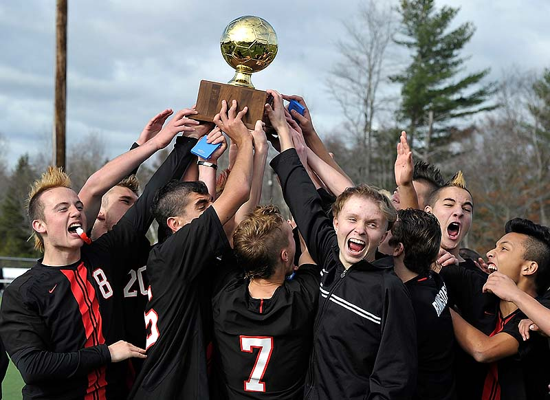 Scarborough holds the Gold Ball after winning the state Class A boys' soccer championship Saturday at Hampden Academy. Scarborough beat Mt. Ararat, 4-0.