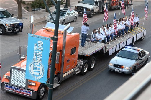 A flatbed truck carries wounded veterans and their families during a parade before it was struck by a train Thursday, Nov. 15, 2012 in Midland, Texas.