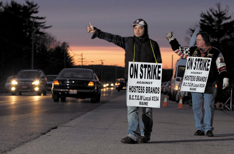 Striking workers Nam Phan, left, and Randy Goodwin picket outside a Hostess Brand plant Friday, in Biddeford.