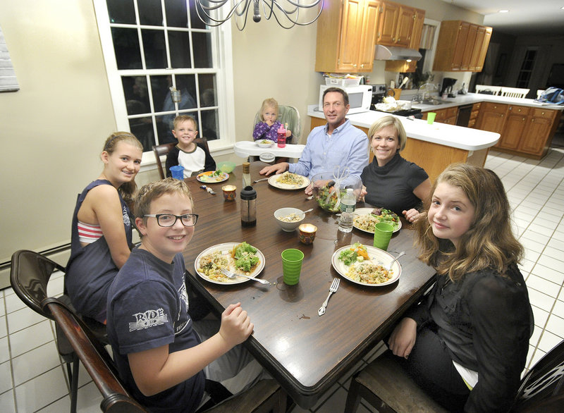 "The Peterson family sits down for a dinner of creamy vegan ""chicken"" casserole with chopped-pumpkin-seed tossed salad recently at their Portland home. Clockwise from lower left, Bryant Peterson, 13, Madison Legassey 13, Brady Peterson, 4, Gabriela Peterson, 2, Jeff Peterson, Laura Peterson and Carly Peterson, 12."