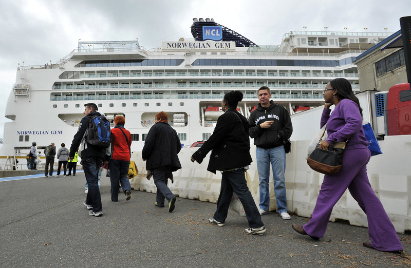 Passengers walk toward the Black Falcon Cruise Terminal in Boston, where they docked on Wednesday.