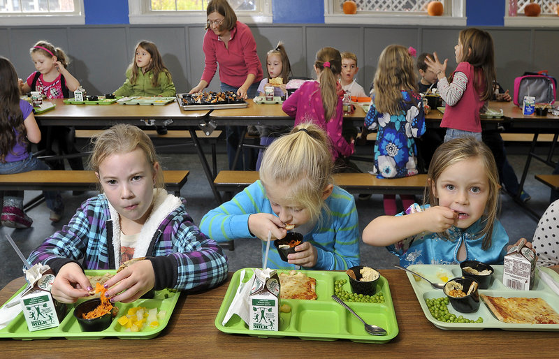 First-graders, from left, Abby Blethroade, Hannah Doram and Addison Brown eat lunch that includes carrot slaw, hummus and pita chips the students in South Berwick helped to prepare. The schoolchildren voted the hummus their favorite.