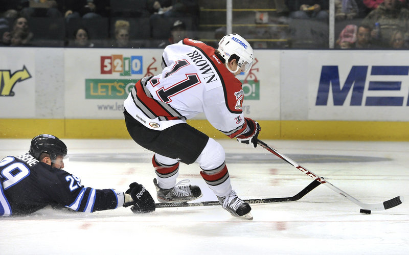 Chris Brown avoids a poke check by Dean Arsene, a former Pirates defenseman, and breaks in alone to score the game's first goal.