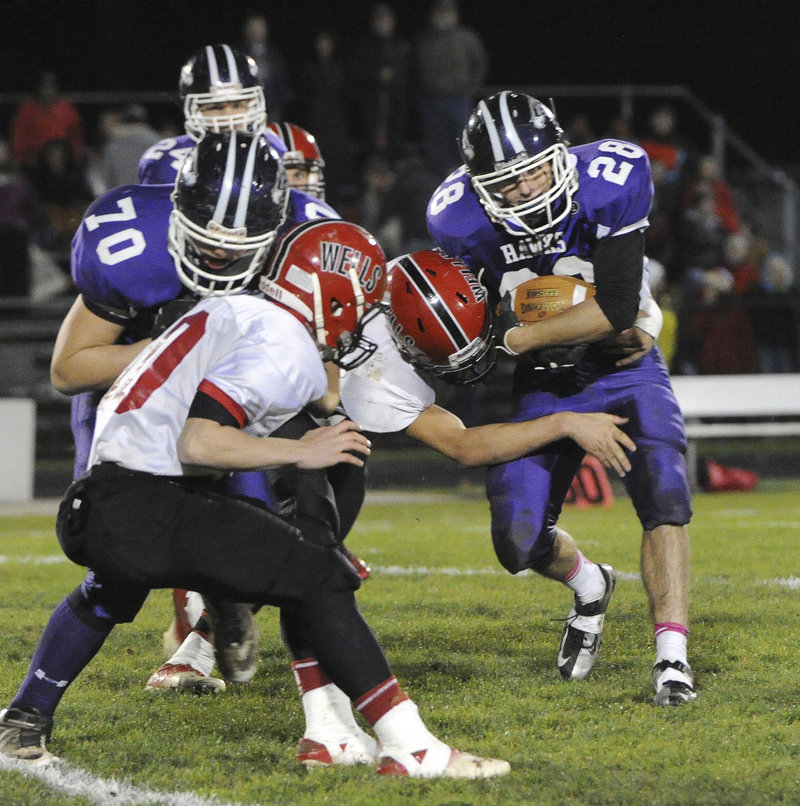 Nick Janes crashes through the Wells defense Friday night. A fine two-way player, Janes also intercepted a fourth-quarter pass to end the Warriors' hopes for a comeback in the Western Class B semifinal in South Berwick.