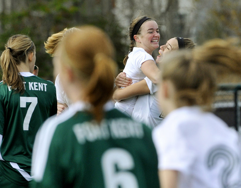 Isabel Agnew, center, gets a hug from Sadie Cole after Cole scored Waynflete's first goal Saturday in the Class C girls' soccer final against Fort Kent. Agnew assisted on Cole's goal, then scored the winner midway through the second half as Waynflete rallied for a 3-2 victory.
